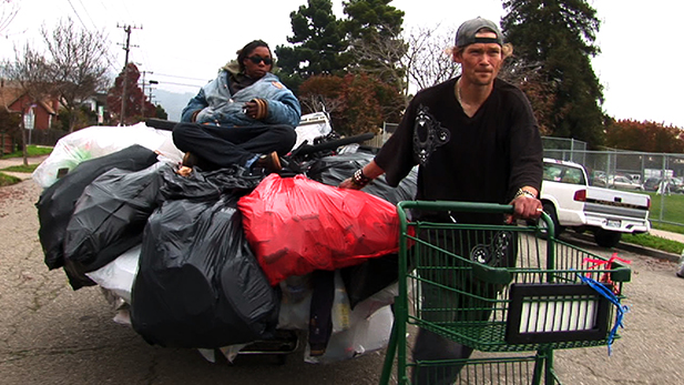 Jason Witt (right) hauls a shopping cart with his girlfriend, Heather Holloman (left), on top.