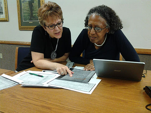 Debbie Weitzell, left, and Stephanie Gelsinon scan Freedmen Bureau documents.