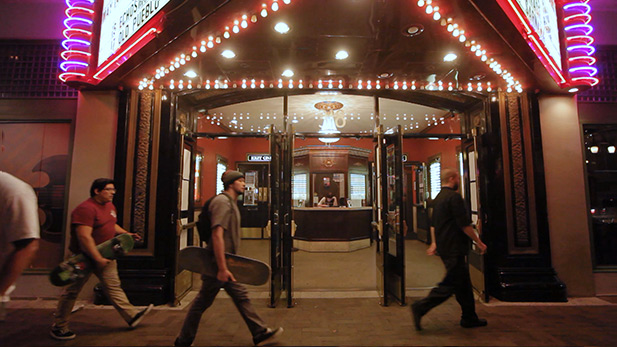 People walk by the entrance to the Fox Theatre in Downtown Tucson at night.