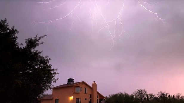 Lightning flashes over a house on Tucson's far east side during a monsoon storm.