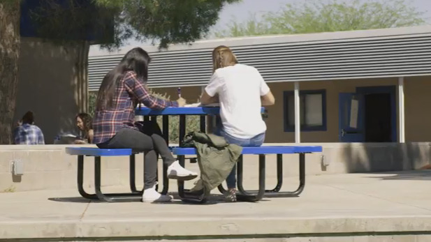 Students at a Tucson High school sit at a table outside.