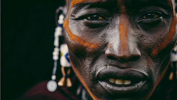 Close up of a Maasai warrior's face pained with ochre.