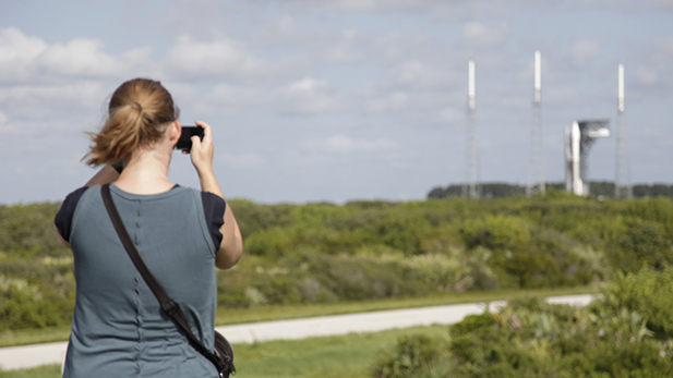 Lori Harrison, OCAMS systems engineer for OSIRIS-REx, photographs the Atlas V rocket on Cape Canaveral the day before the scheduled launch.