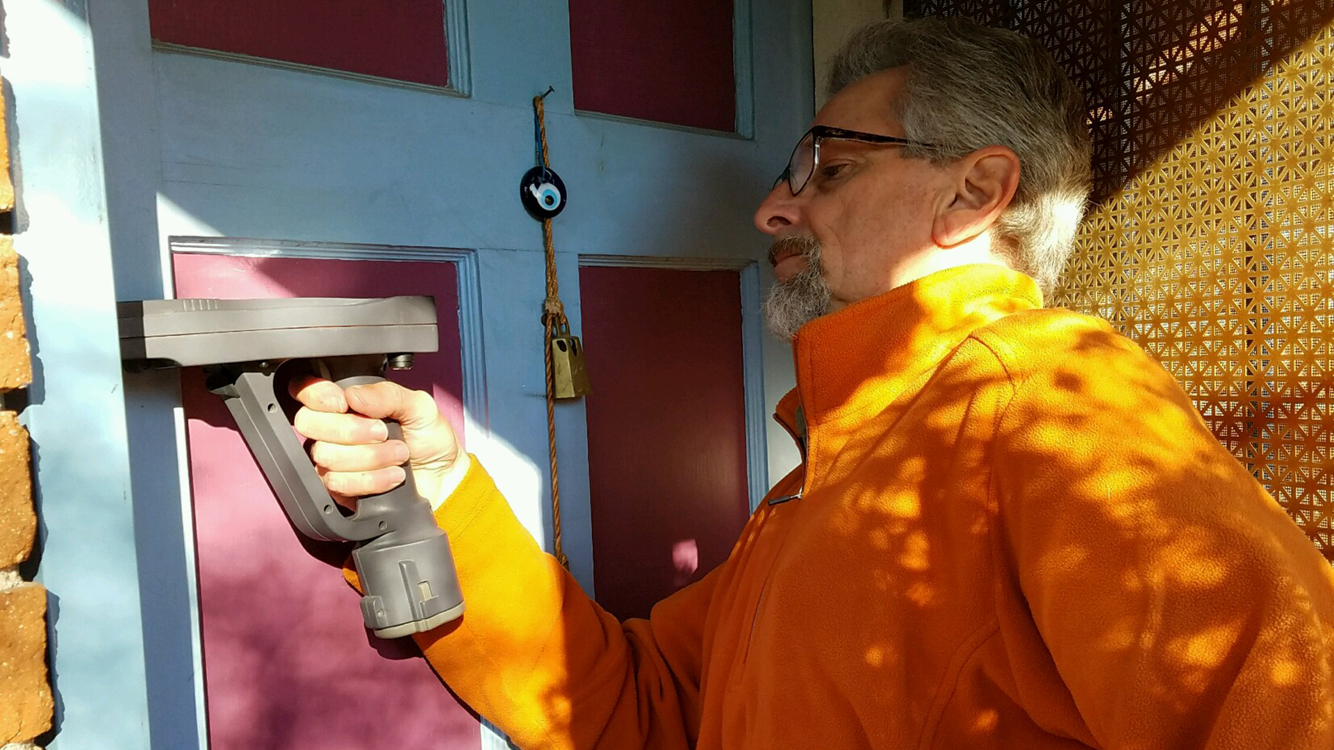 Chuck Phelan uses an XRF gun to test a home's door jamb for traces of lead. Homes are considered positive for lead if they test at a level of one milligram of lead per square centimeter.