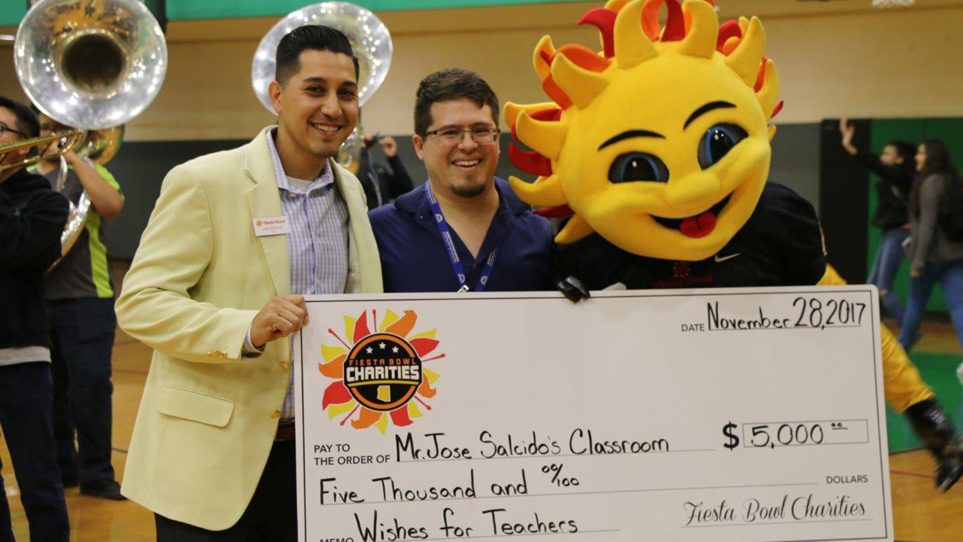"Fiesta Bowl representative José Moreno presents the check to teacher José Salcido with ""Spirit,"" the Fiesta Bowl mascot."