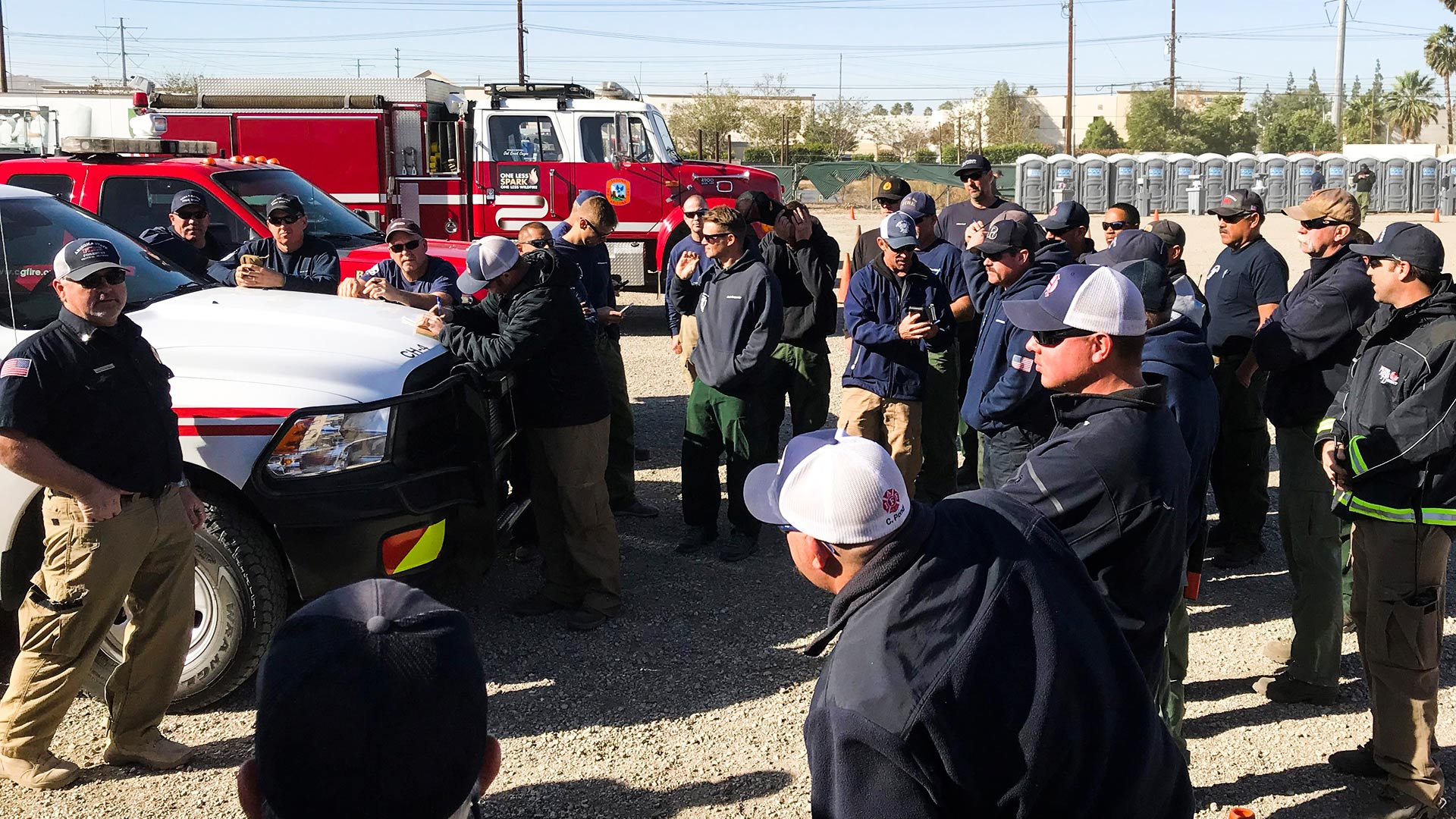 Department of Forestry and Fire Management Central District Manager Dan Colgan, far left, briefs Arizona crews set to fight fires in California, Dec. 6, 2017.
