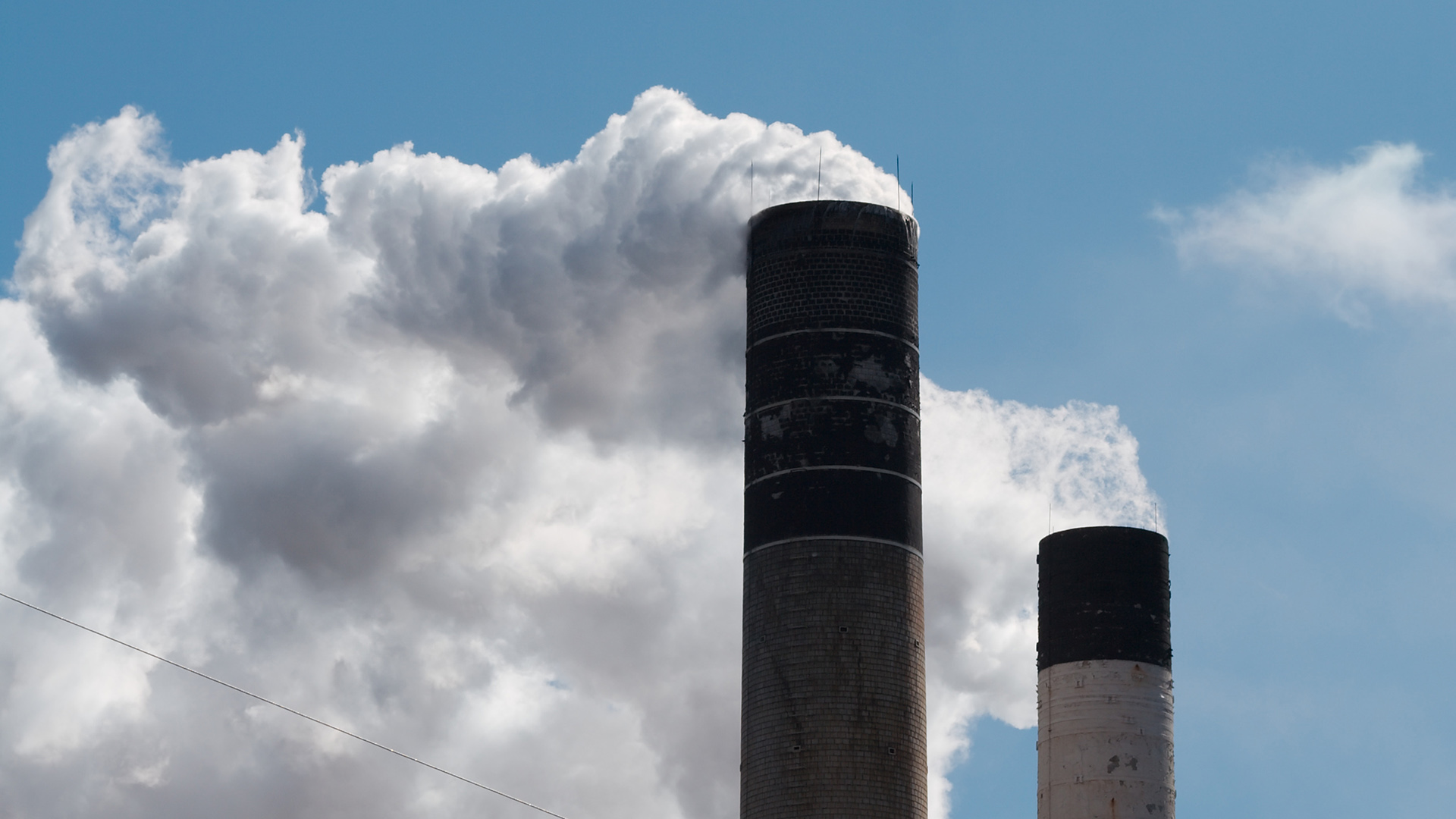 Smokestacks emit smoke into a blue sky.