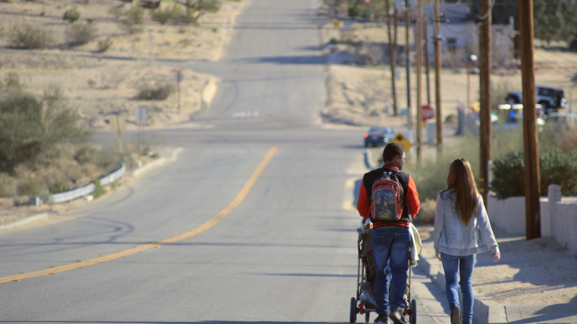 Students Lee Bridges and Layla Schneider walk with their baby towards a bus stop in Twentynine Palms, CA.