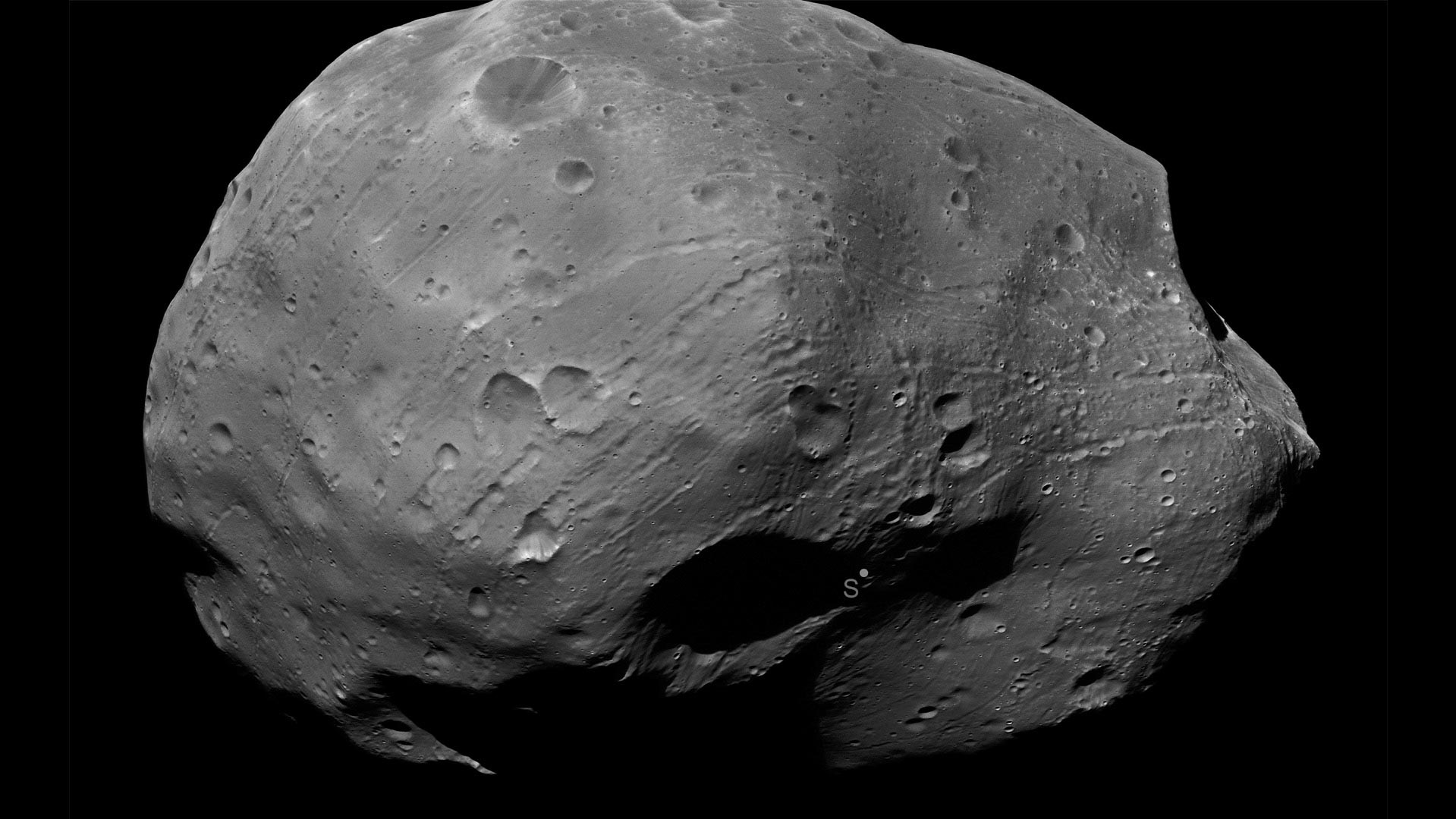 "Phobos is a moon of Mars, a body that a team from the Planetary Science Institute could study in the name of future exploration. The ""S"" in the image indicates the south pole of the moon."