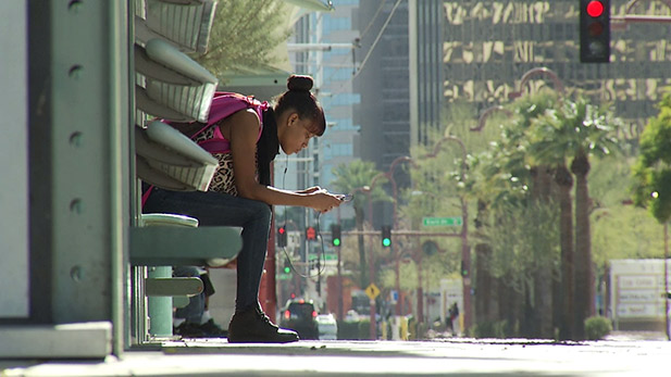 A young black woman waits for the streetcar at a stop in downtown Tucson.