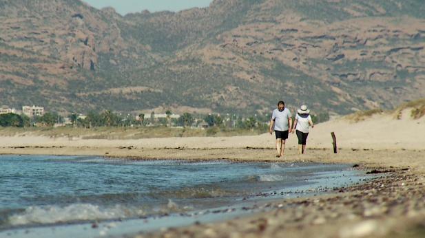 Couple on beach at San Carlos, Mexico, spotlight
