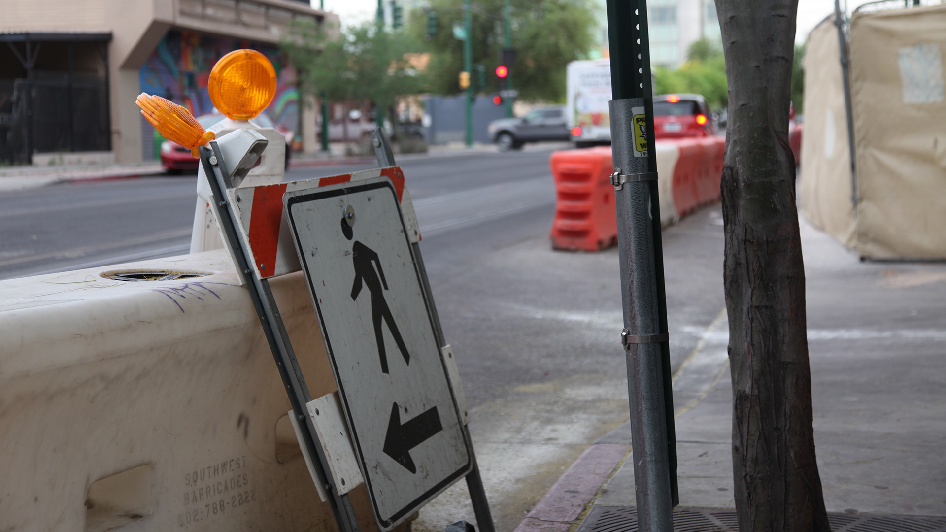 A sign directing pedestrians on a street in downtown Tucson.