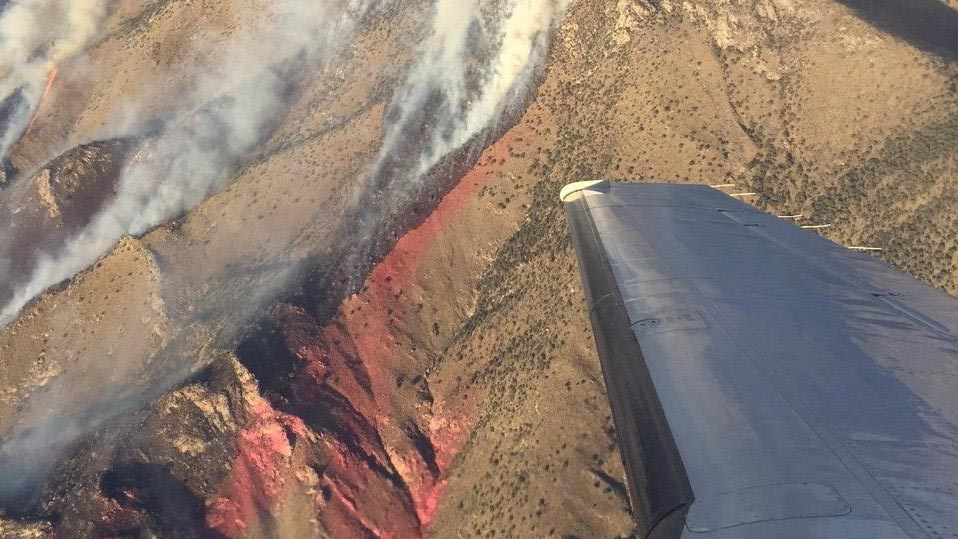 Sawmill Fire burning up ridge lines near Sonoita. Red tinge is residue of fire retardant dropped from air tankers.