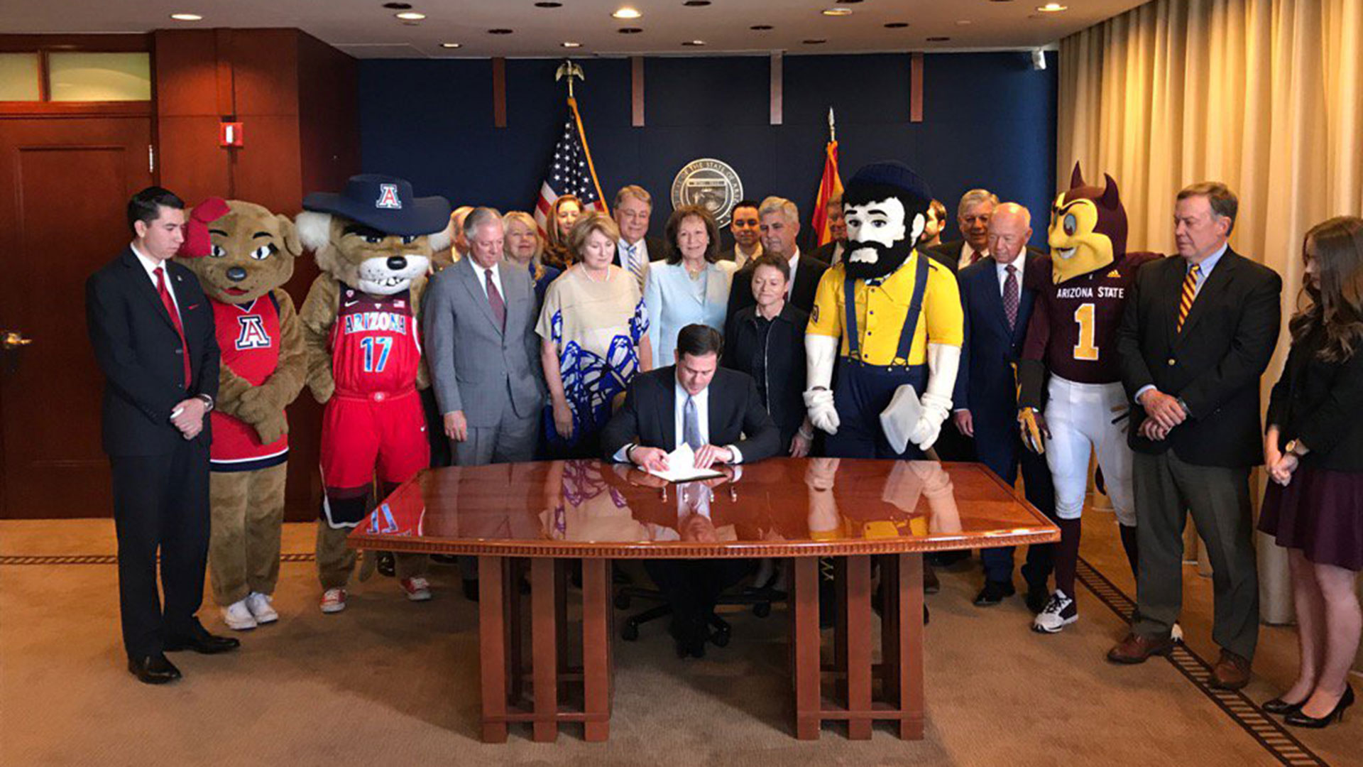 Arizona Gov. Doug Ducey, accompanied by Arizona regents, university officials and others, signs a plan to create a borrowing package to fund university maintenance, May 22, 2017.