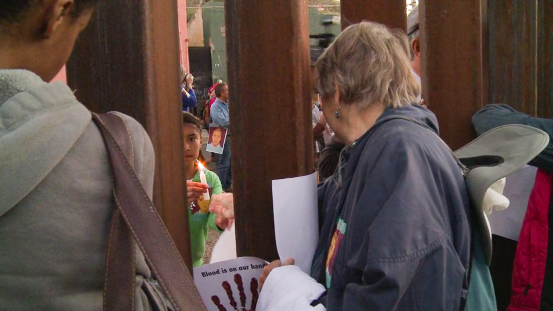 A woman passes a candle from Nogales, Arizona, through the border fence to a child at an April 2013 protest over the death of Jose Antonio Elena Rodriguez.