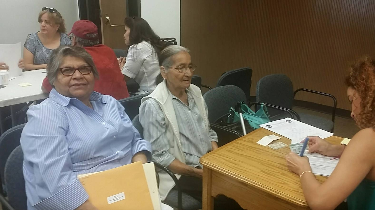 Ildi Flores, center, and Amanda Castro, left, a friend, meet with a volunteer to start the paperwork for Flores' citizenship in Nogales, May 2017.