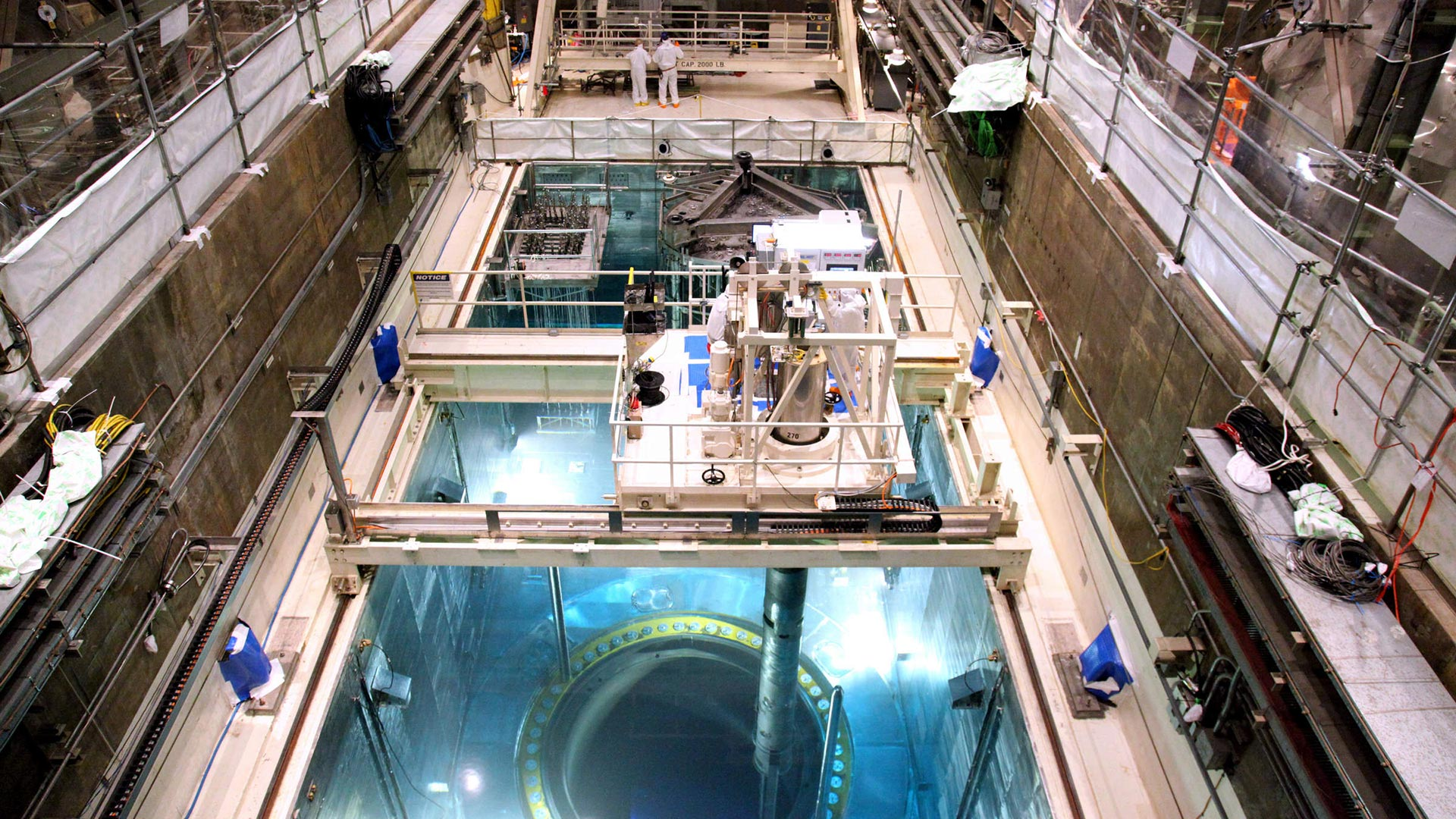 The deep blue of Cherenkov radiation reveals the location of the fuel assemblies within the open reactor core (foreground). The tube beneath the platform, a tube-shaped fuel handling machine extracts one of these assemblies.