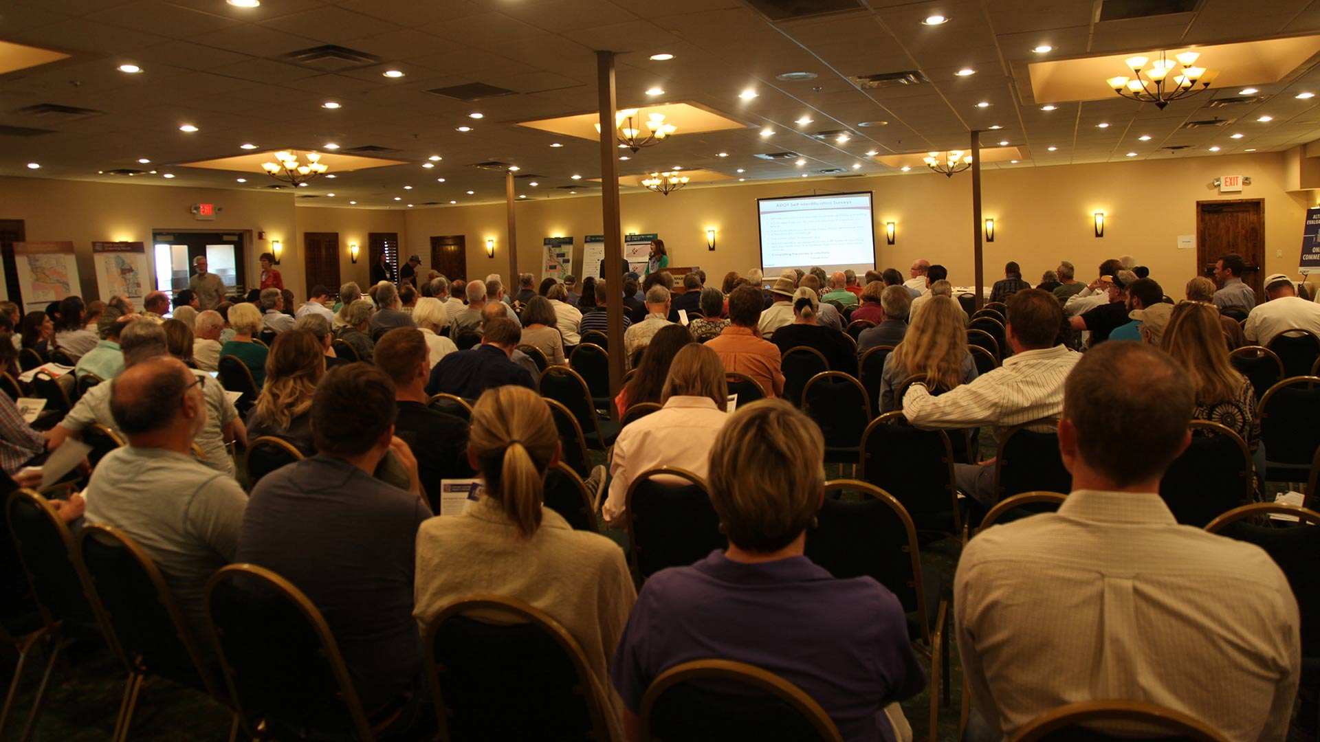 People listening to a presentation at an ADOT public meeting on Interstate 11 in Tucson.