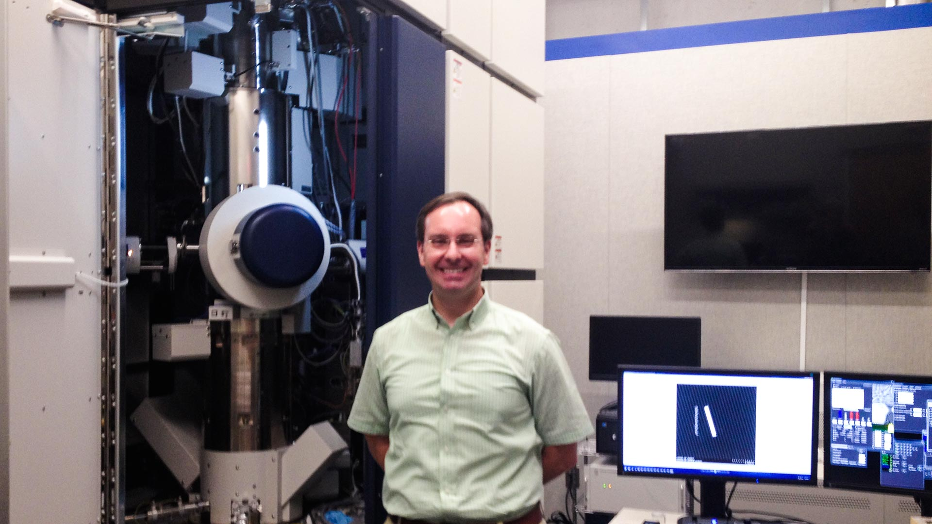 Planetary scientist Tom Zega with the UA Lunar and Planetary Laboratory's transmission electronic microscope which will analyze dirt samples returned from the asteroid Bennu in 2023. The instrument has serial number 1.