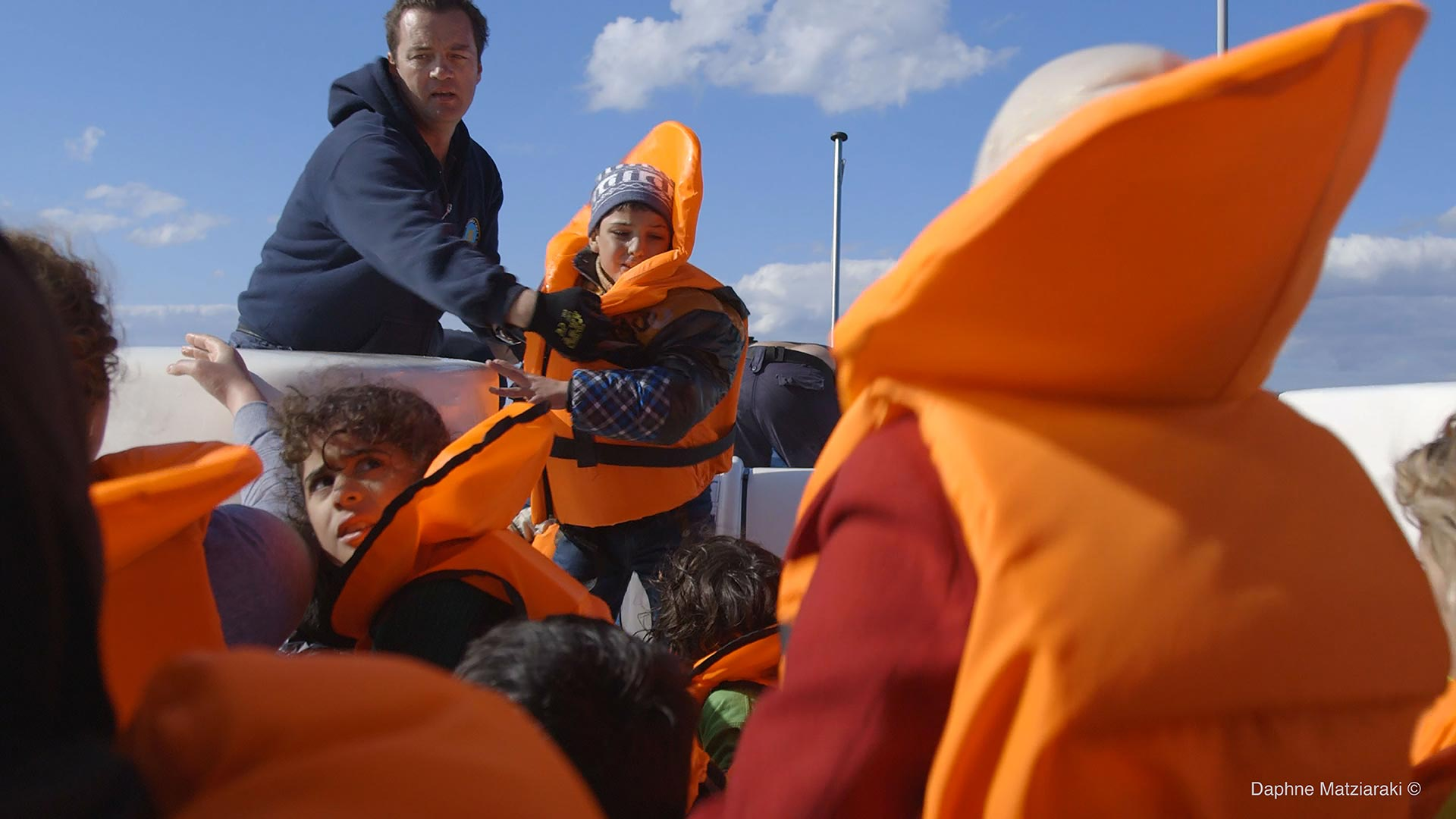 Captain Kyriakos Papadopoulos is pulling a Syrian boy from a dingy boat that just got rescued.