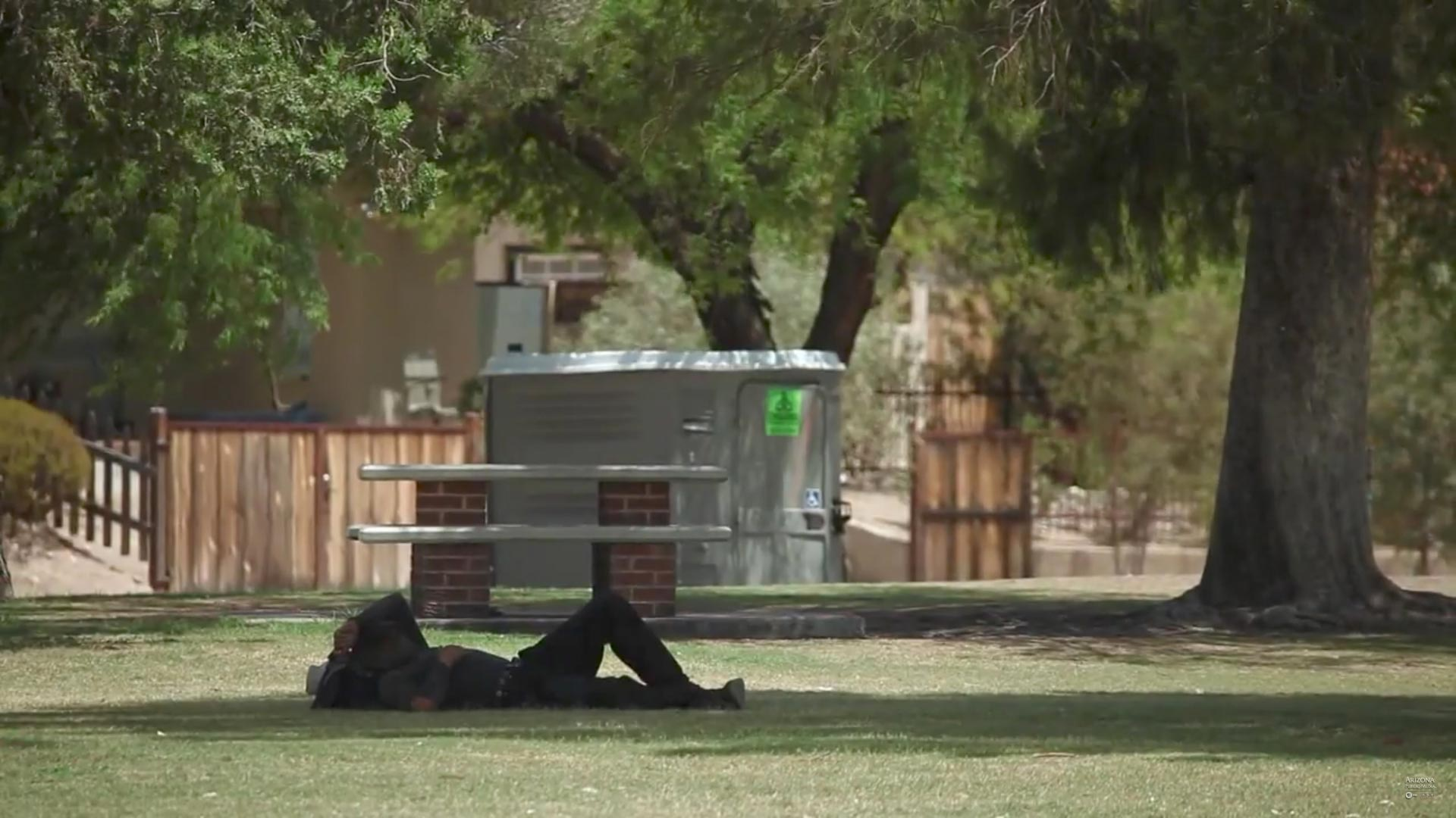 A man rests in the shade on a hot day in Tucson.