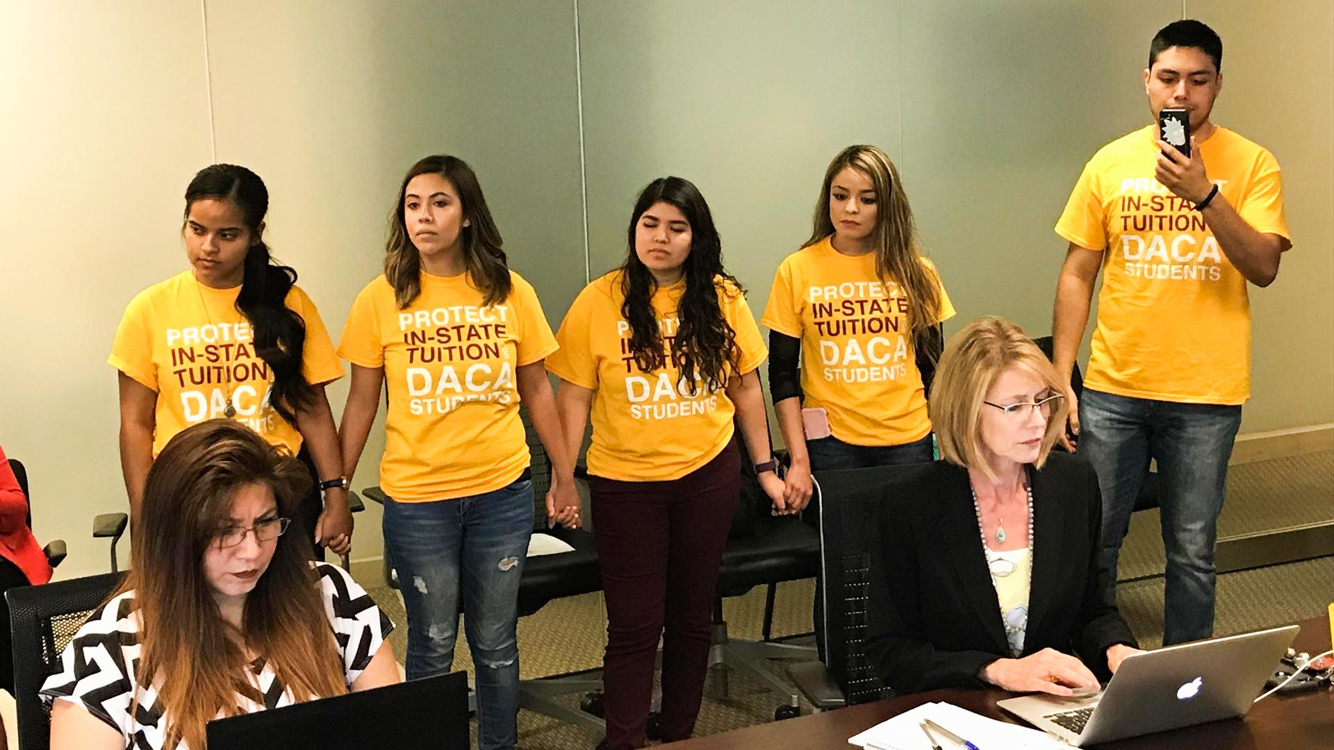A group stands in support of in-state tuition eligibility for students in Arizona with DACA status at a June 29 Arizona Board of Regents meeting.