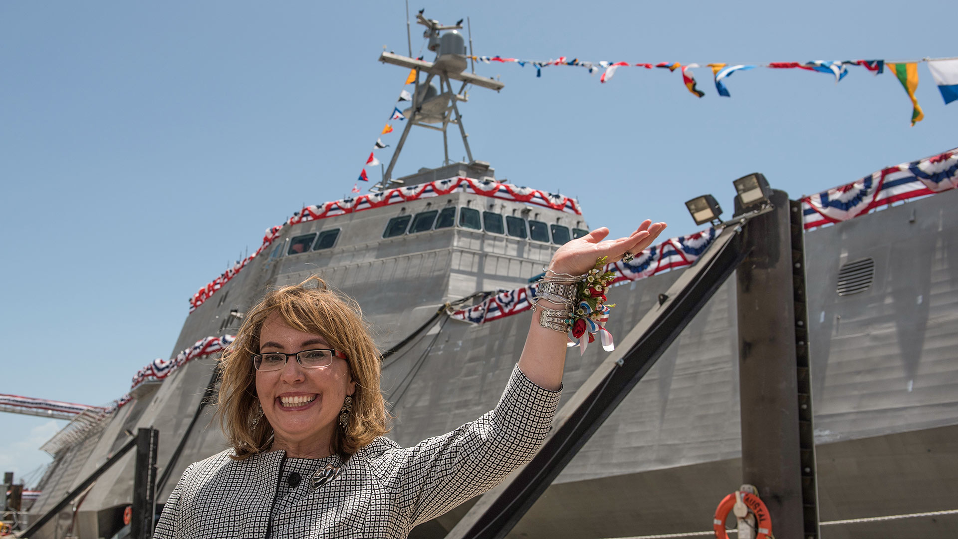 "Former U.S. Rep. Gabrielle ""Gabby"" Giffords waves to a crowd in front of the littoral combat ship, USS Gabrielle Giffords (LCS 10), named for her. Giffords was on the stage as Dr. Jill Biden christened the ship at Austal USA in Mobile, Ala. The 419-foot ship was built at the Austal shipyard and is the Navy's 10th littoral combat ship designed to operate in shallow waters near the coast. It is 16th U.S. naval ship to be named for a woman and only the 13th since 1850 to be named for a living person. June 13, 2015"