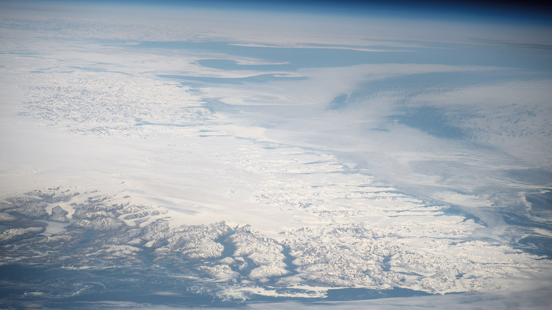An aerial photo of the southern tip of Greenland's ice sheet, surrounded by glacier-carved fjords. UA scientist Jack Reeves Eyre says the island's ice melt could significantly raise sea levels in the next 50 years.