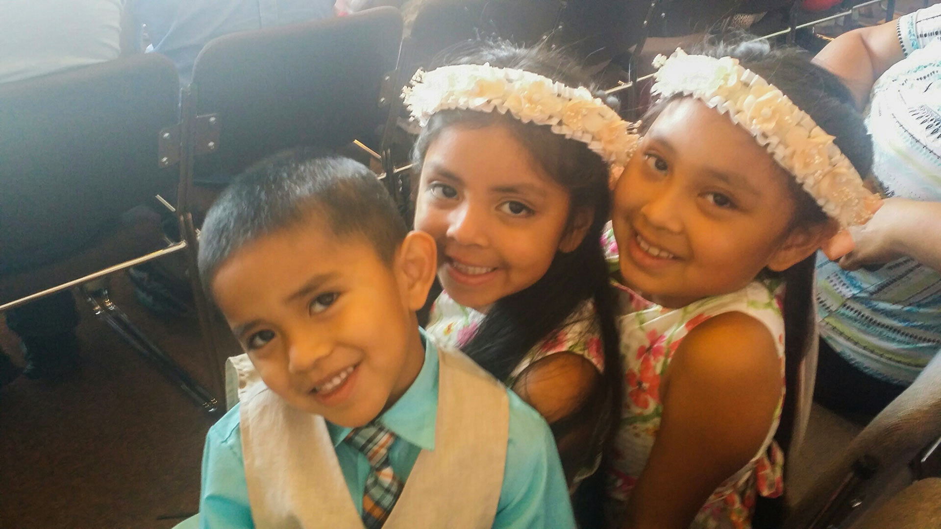 Three siblings watch as mother keeps her promise to become a U.S. Citizen.