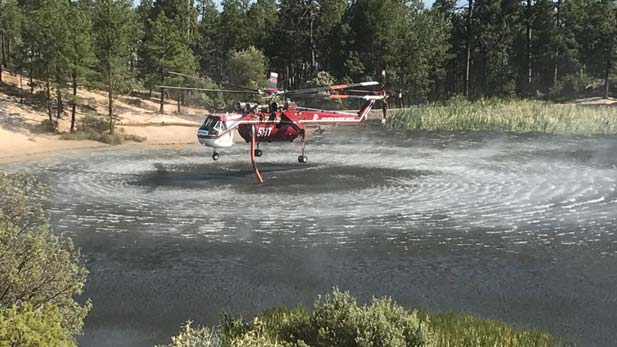 A helicopter hovers above a lake to refill on water.