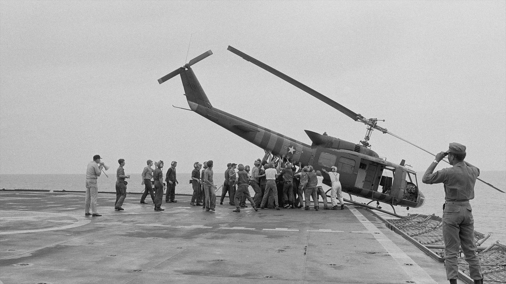 U.S. Navy personnel push a helicopter into the sea to make room for more evacuation flights from Saigon. April 29, 1975.