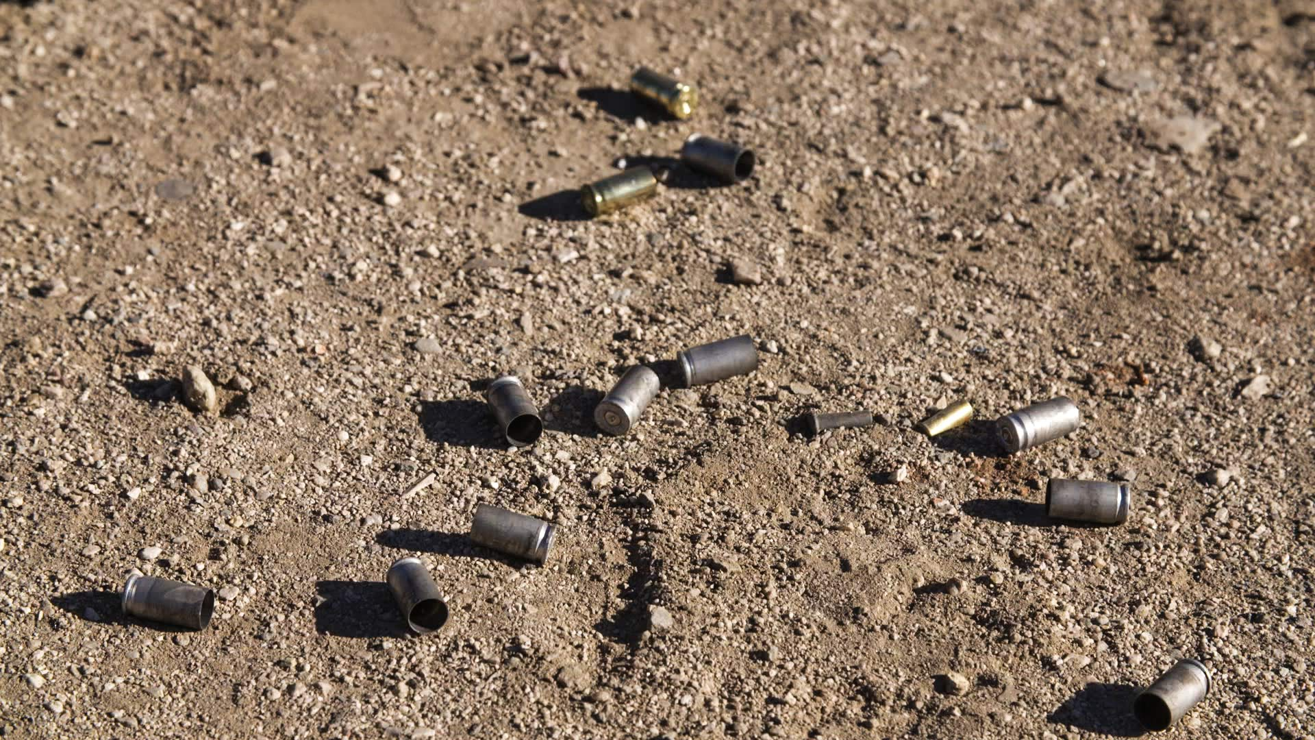 Bullet casings on ground at an outdoor firing range.