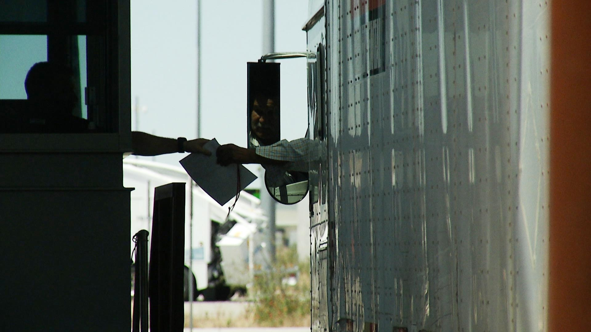 A trucker passes a document to an official while crossing the U.S.-Mexico border.