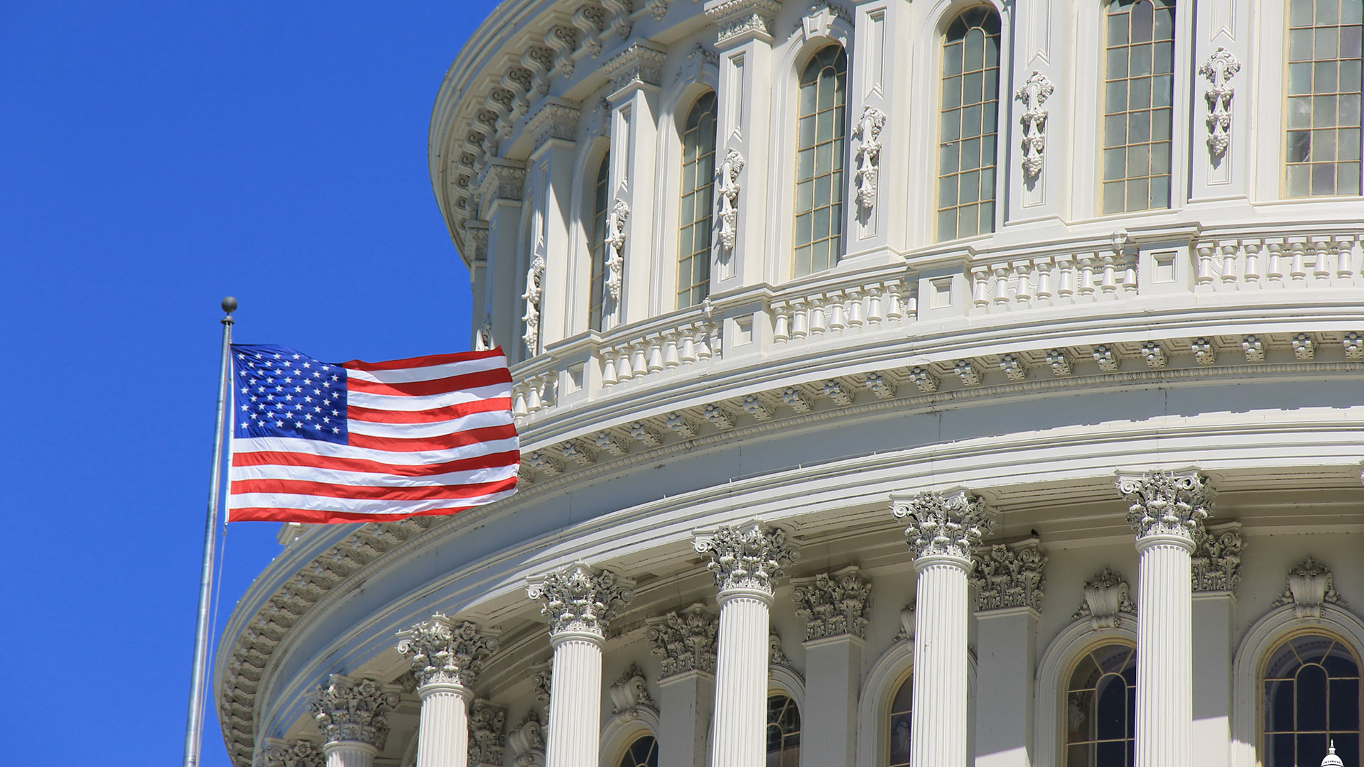 A flag flies by the dome of the U.S. Capitol.