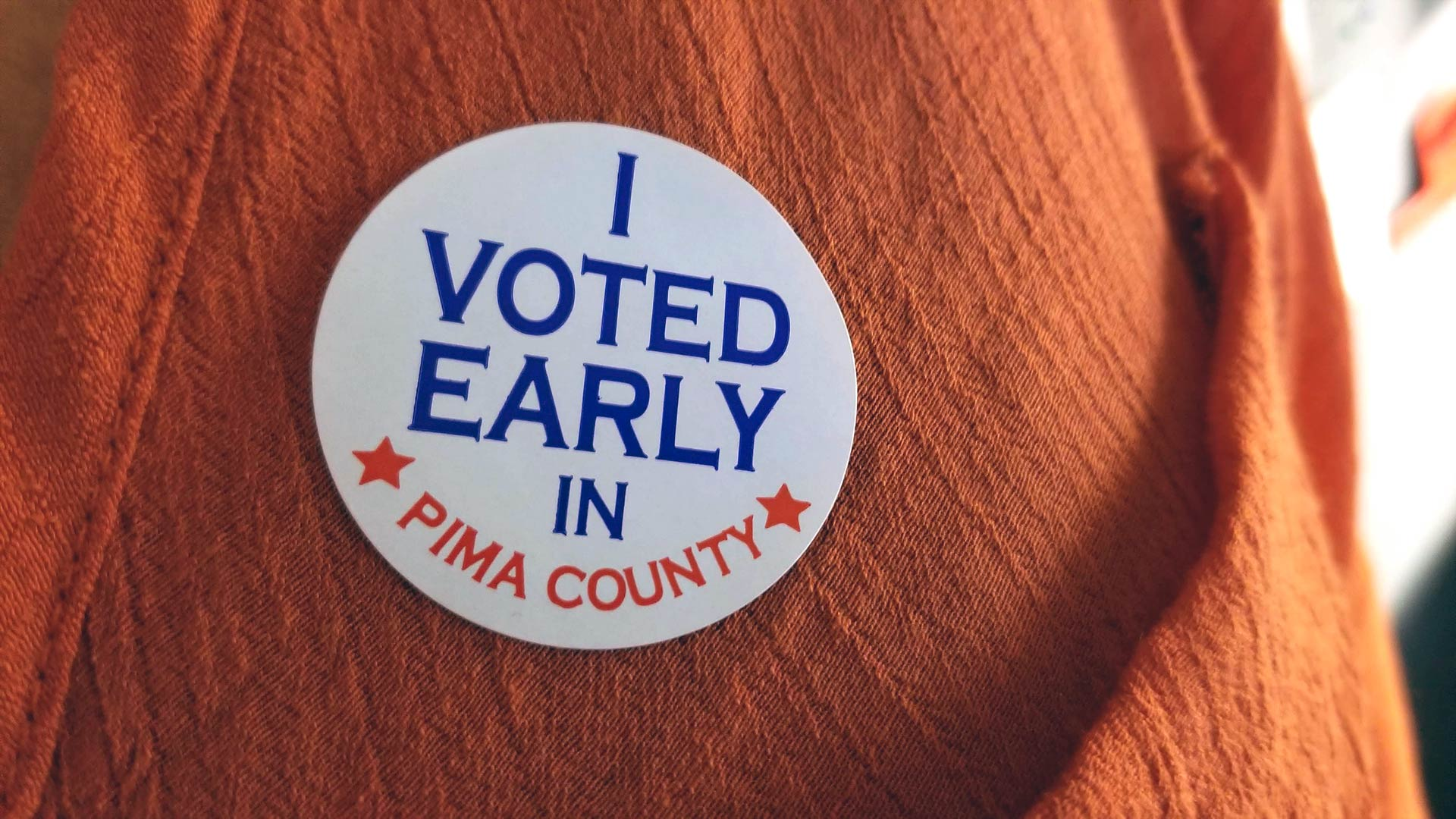 "A voter displays their ""I Voted Early in Pima County"" sticker."