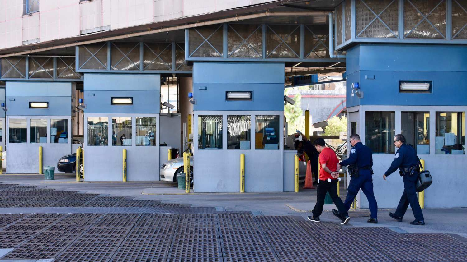 Customs and Border Protection officers lead an unidentified man away in handcuffs at the Nogales downtown port of entry last Friday.