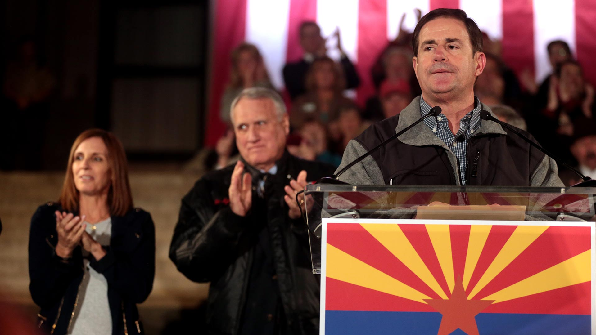 Gov. Doug Ducey speaks at an event on the eve of the election, 2018. Behind him are Martha McSally and Jon Kyl.