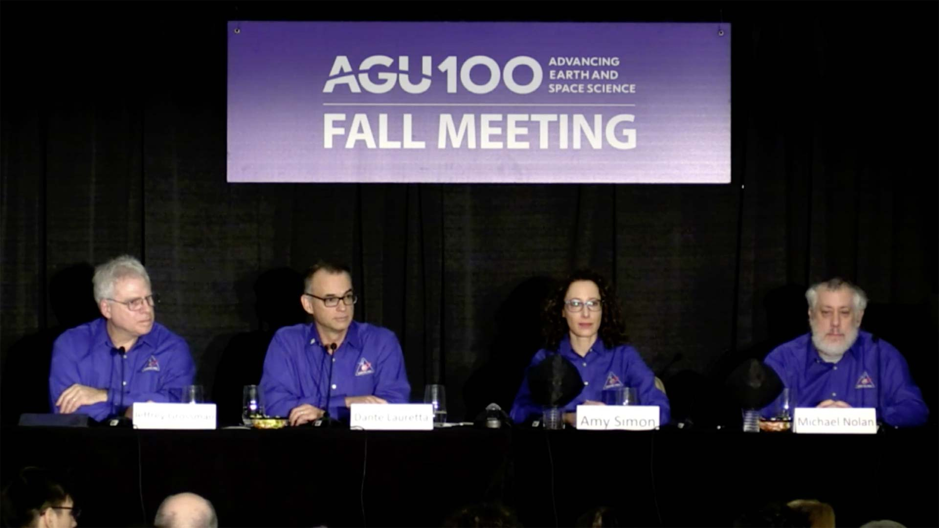 Scientists announce water findings in the clay of the asteroid Bennu in this still image from a livestream of the American Geophysical Union's 2018 Fall meeting.