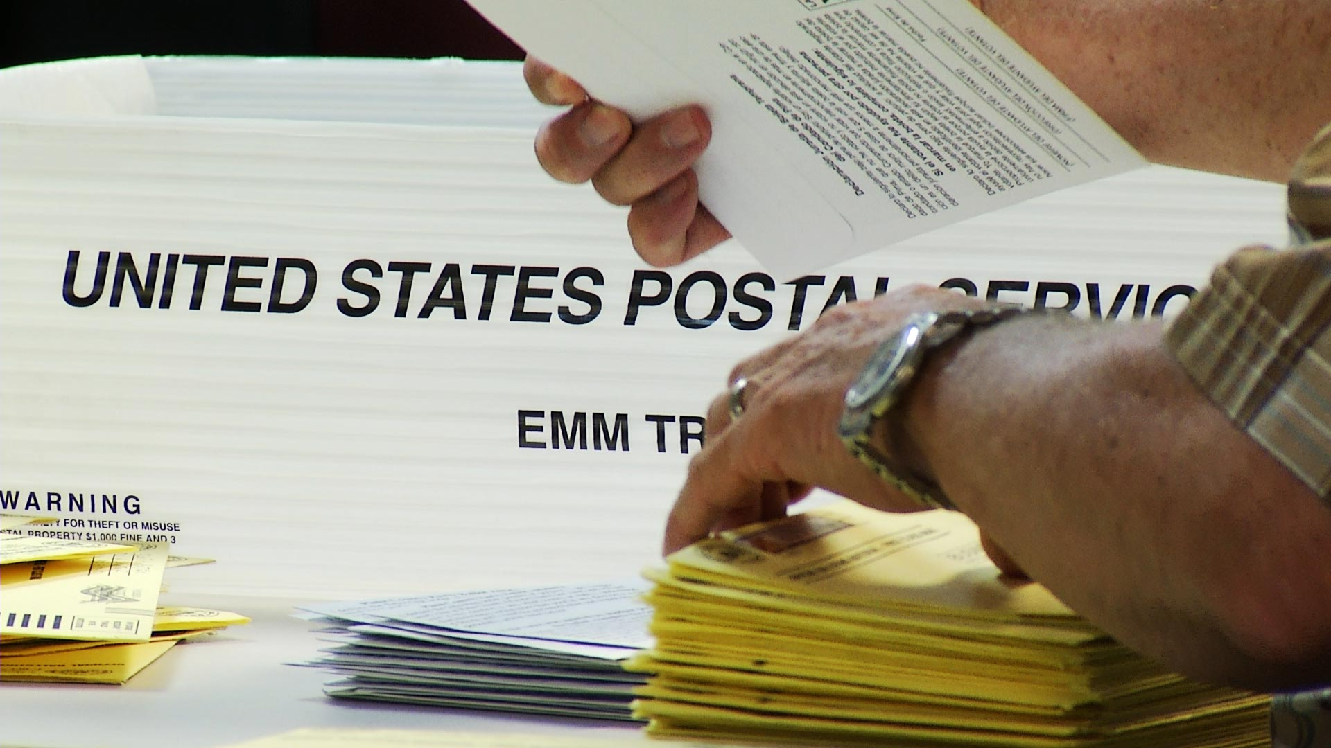 A file image of a volunteer sorting mail ballots in Pima County.