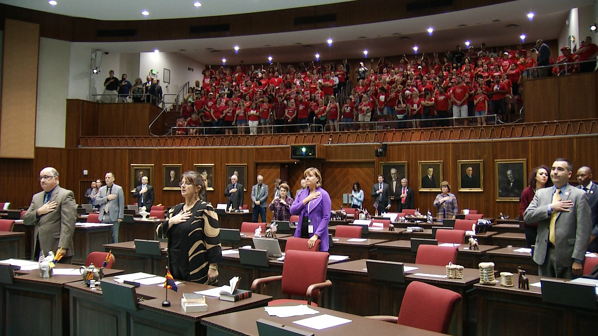 Arizona House lawmakers stand for the Pledge of Allegiance with members of the Red for Ed movement watching from the gallery above on April 30, 2018.