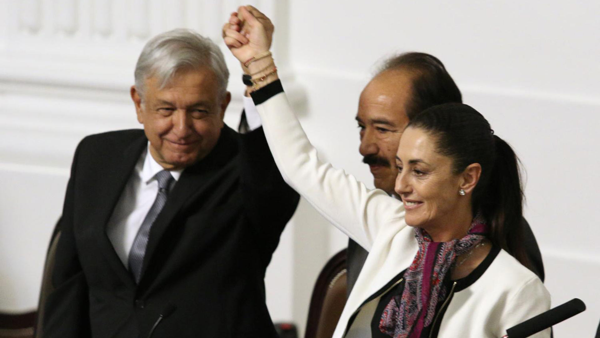 Claudia Sheinbaum Pardo, Mexico City's first elected female mayor, holds up a hand with President Andrés Manuel López Obrador as Mexico City Congress President José de Jesús Martín del Campo looks on.