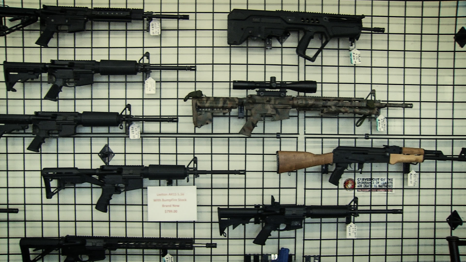 Guns for sale hang on the wall of a Tucson store.