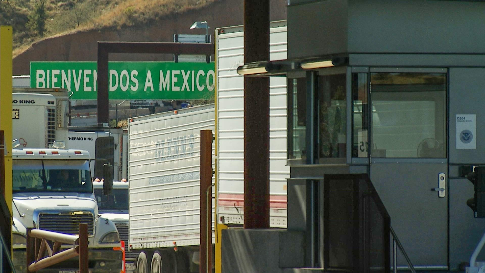"Trucks wait in line to cross into the United States via Nogales, while a sign reading ""Bienvenidos a México"" welcomes those crossing into Mexico."