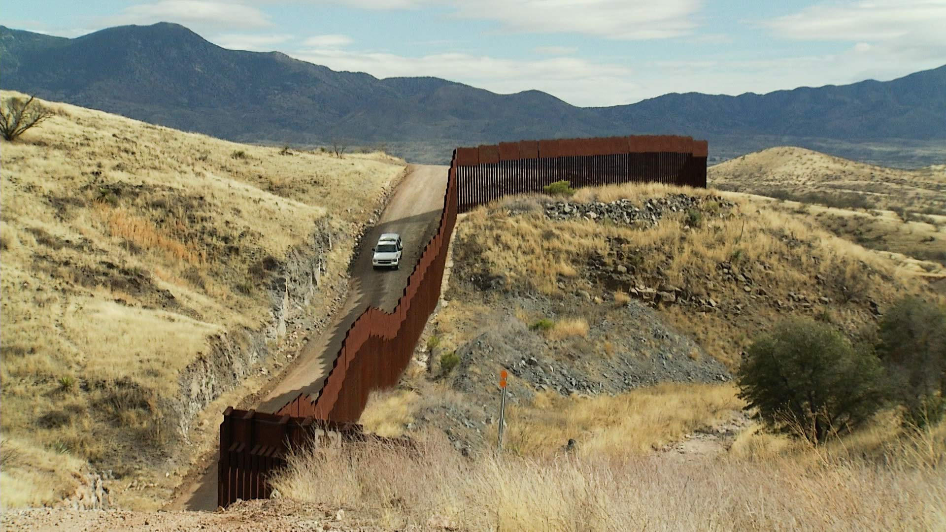 A Border Patrol vehicle travels along a stretch of fence along the U.S.-Mexico border.