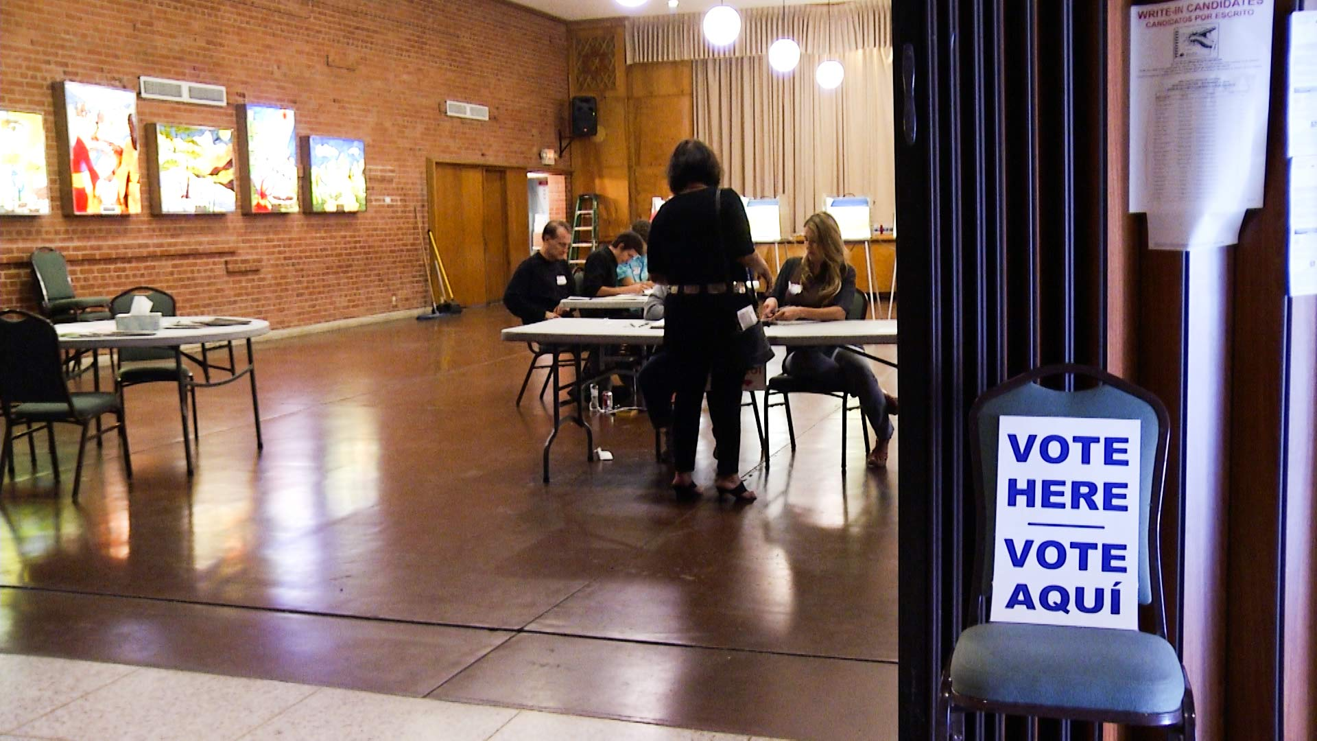 Volunteers check voter registration at a voting station.
