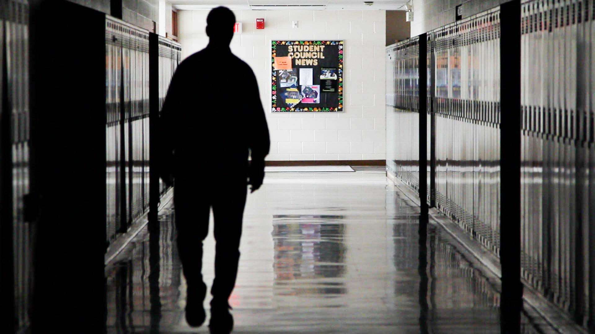 A student walking down a hallway.