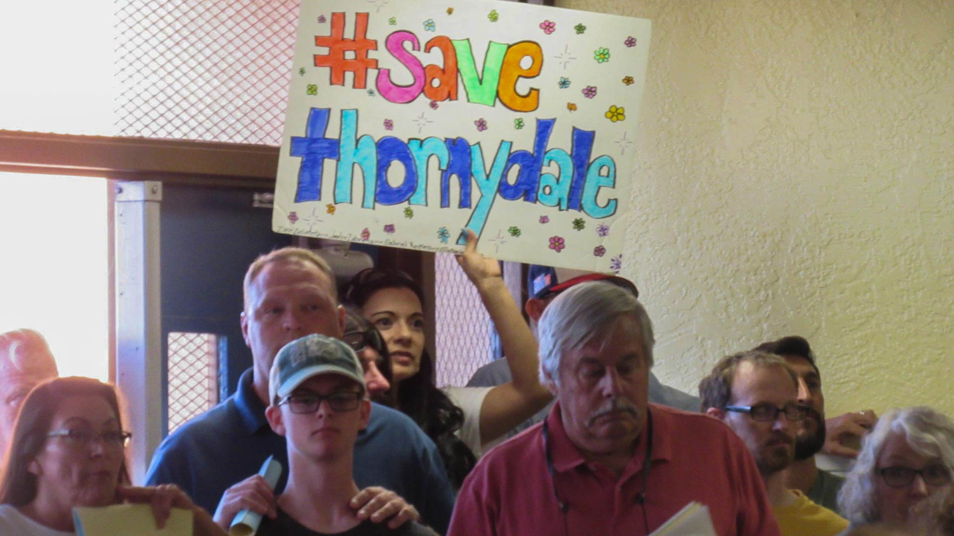 A parent at holds up a sign at a public meeting on the future of Thornydale Elementary.