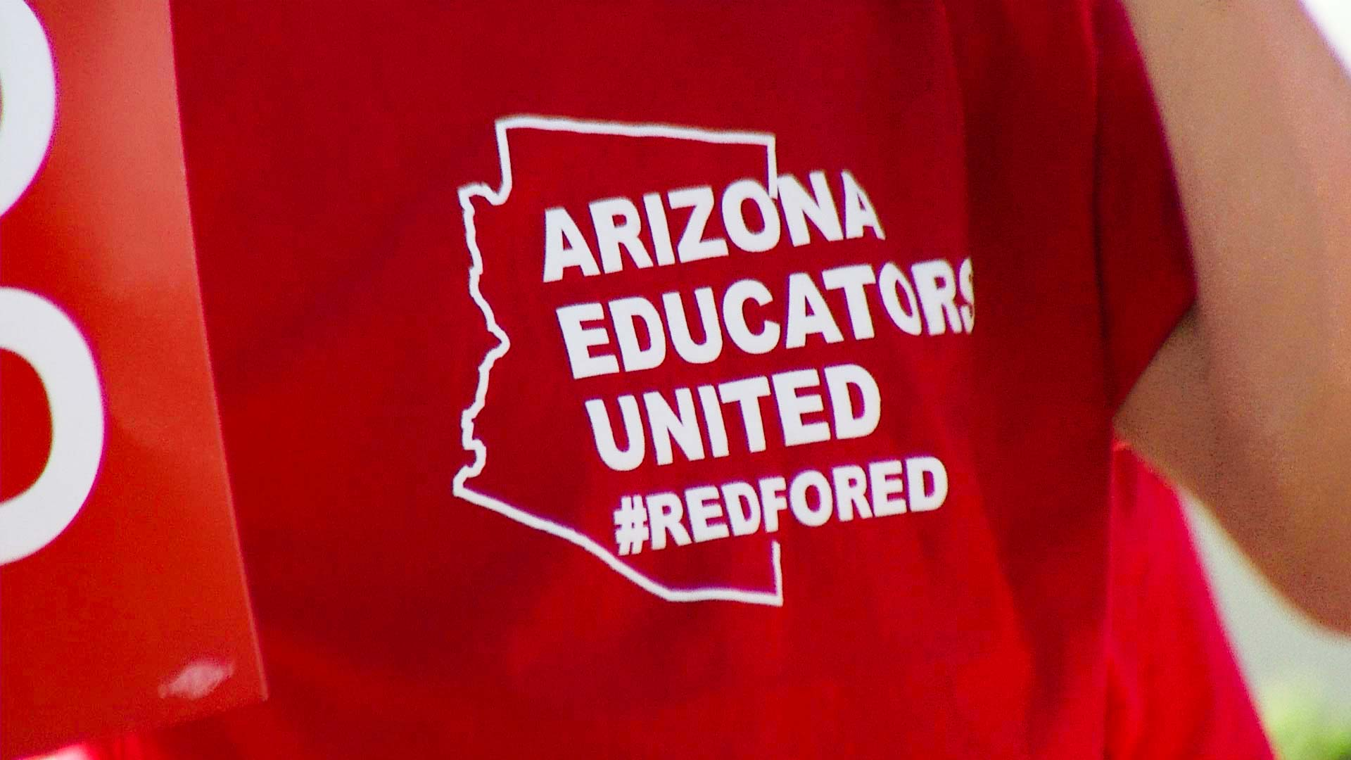 A teacher wears an Arizona Educators United shirt during a walk-in demonstration.