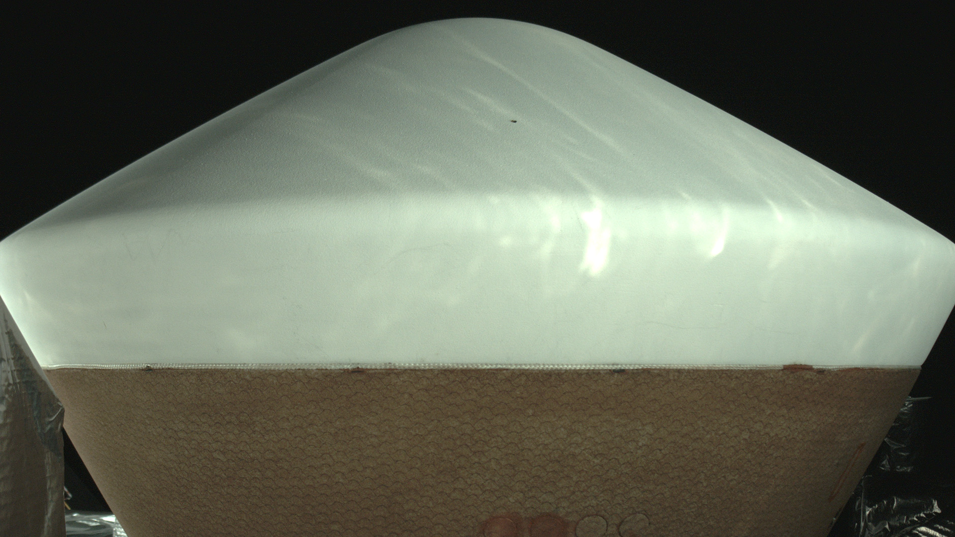 A poppy-seed-sized dent (the black spot near the top) was discovered on the heat shield of the OSIRIS-REx sample-return capsule in an image taken by an on-board camera March 2, 2017. The damage won't affect the capsule's performance.