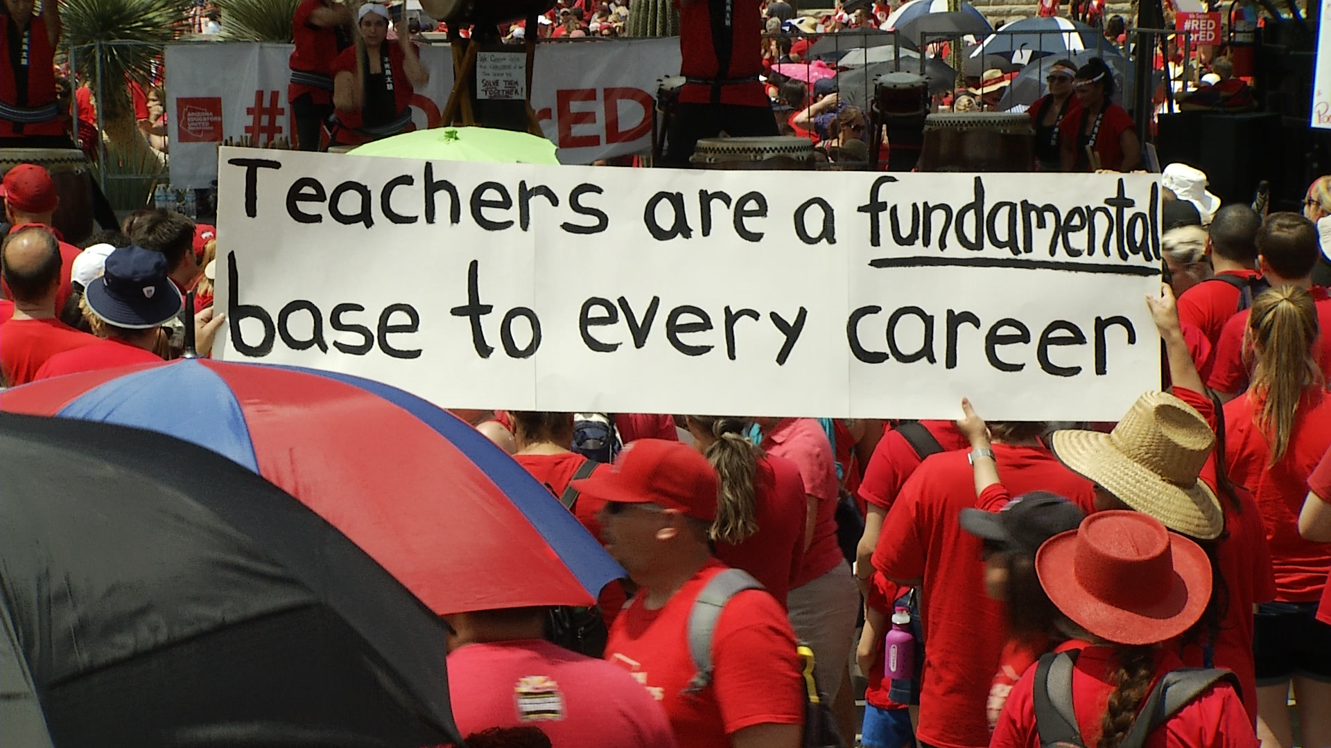 Demonstrators with the Red for Ed movement hold a banner supporting educators outside of the Capitol in Phoenix.